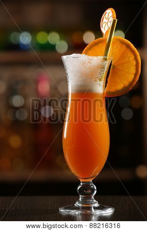 Glass of fruit cocktail in bar on bright blurred background