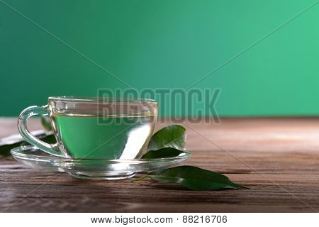Cup of green tea on table on green background