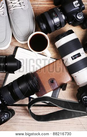 Modern cameras on wooden table, top view