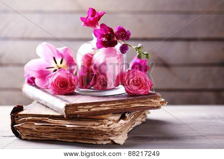 Beautiful composition with flowers and old books on grey wooden  background