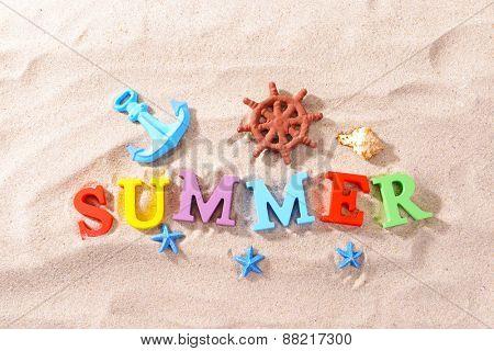 Word summer on beach background