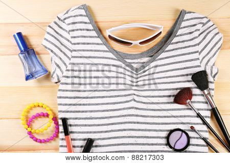 Female shirt and cosmetics on wooden table, top view