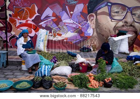 Unidentified indigenous women selling vegetables in the popular Otavalo market, Ecuador