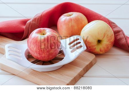 Apples and slicer on a wood background