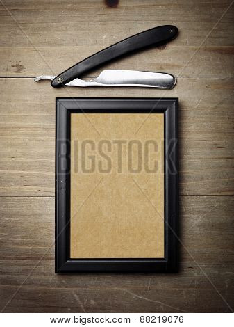 Straight Razor And Kraft Poster On Wood Desk