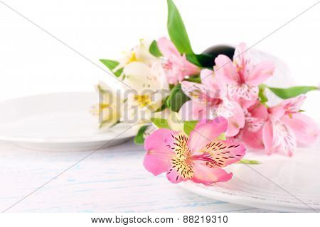 Table setting with flowers, isolated on white