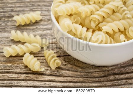 healthy, gluten free quinoa pasta (fusilli)  - small ceramic bowls against grained wood