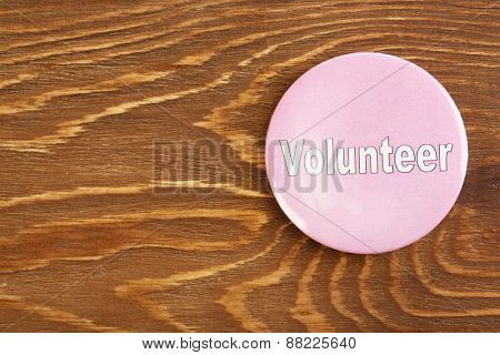 Round volunteer button on wooden background