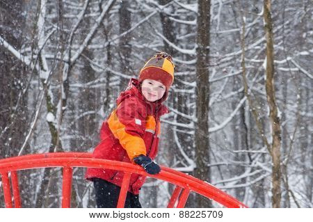 Cute Child Playing In A Snowy Park