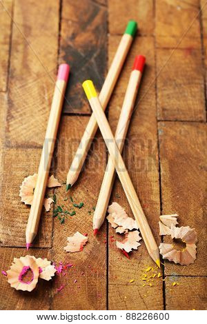 Wooden colorful pencils with sharpening shavings on wooden table