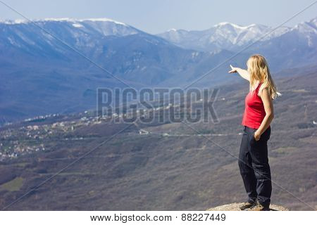 girl standing and showing on a cliff in the mountains