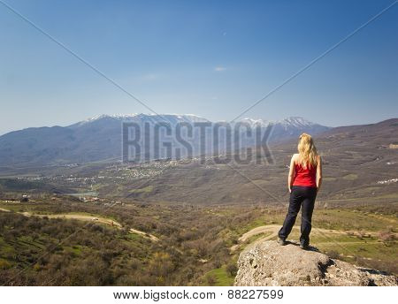 girl standing on a cliff in the mountains