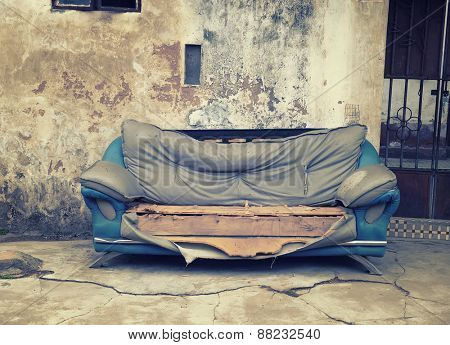 old abandoned house front with blue sofa