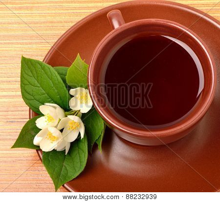 Tea On The Ceramic Cup With Jasmine Flower On The Wood