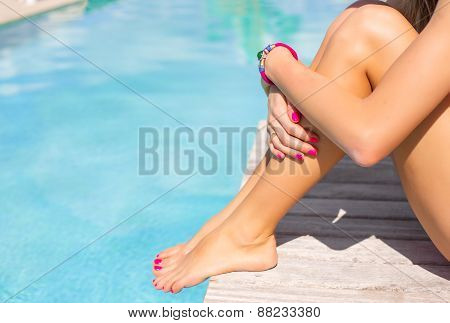 Woman sitting on the deck by the swimming pool