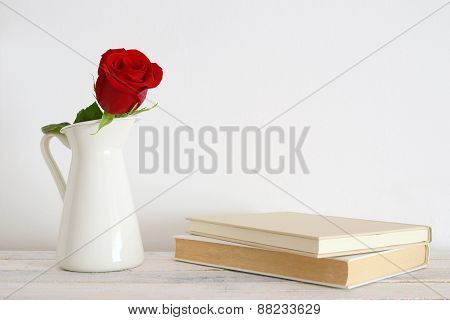A rose in a white vase beside two books
