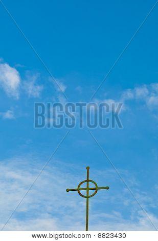 Simple Copper Cross against a Blue Sky