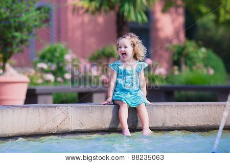 Little Girl Refreshing In A Fountain