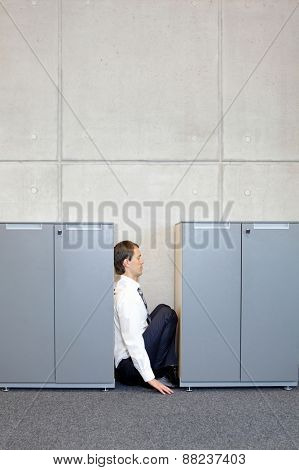 white sad business man crouching between cabinets
