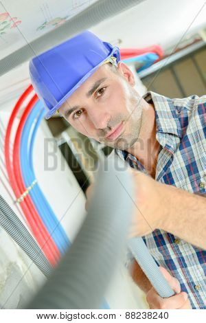 Electrician working through an open ceiling hatch