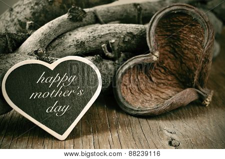 a heart-shaped chalkboard with the text happy mothers day written in it and a heart-shaped fruit shell and some logs in the background, on a rustic wooden surface