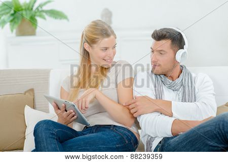 Couple relaxing on the sofa with gadgets