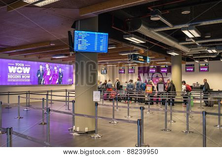 KEFLAVIK, ICELAND - MARCH 15, 2015: WOW Air's passengers waiting for check-in in Keflavik International Airport