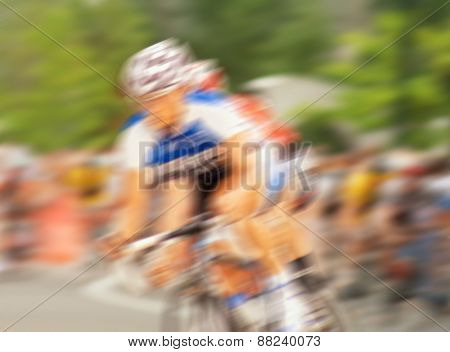 blurred image of a pack of bicycle riders rounding a corner in a bike race