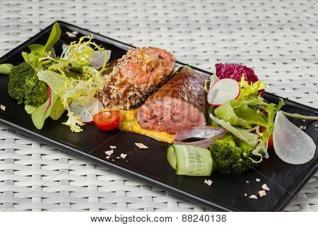 Veal sauce with vegetables on dark plate