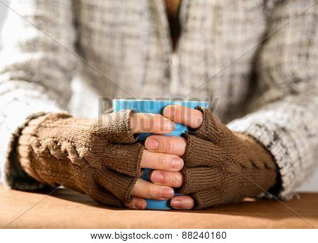 Hot drink in a blue mug in hands with gloves on close up