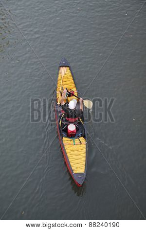 a kayaker in a kayak or canoe paddling down a river