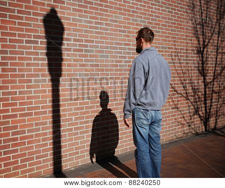 a man looking at his shadow on the stone and brick wall at sunset time