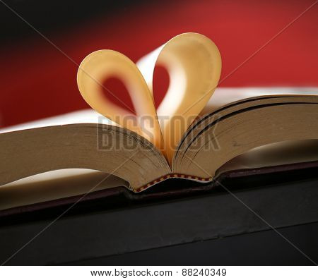 Heart from book pages with a shallow depth of field and a red background