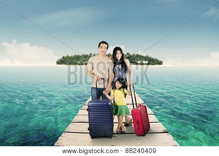 Happy Family Standing At Resort Bridge