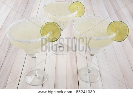 High angle view of three margarita cocktails on a rustic white wood table. Horizontal format. Cinco de Mayo theme.