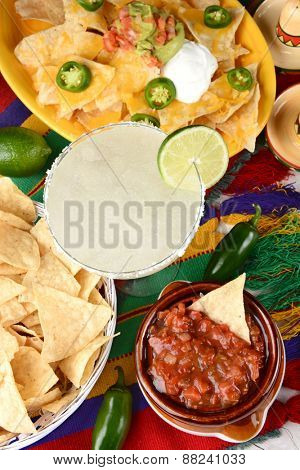 Overhead view of a margarita cocktail surrounded by nachos, chips, salsa on a bright Mexican, table cloth. Vertical format. Cinco de Mayo theme.
