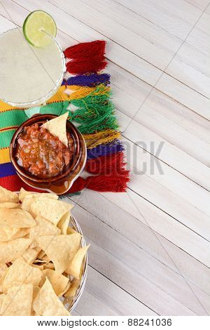 Overhead view of a margarita cocktail with chips and salsa on a white rustic wood table. Vertical format with copy space. Cinco de Mayo theme.