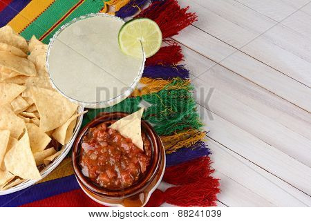 High angle view of a margarita cocktail with chips and salsa on a white rustic wood table. Horizontal format with copy space. Cinco de Mayo theme.