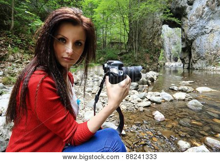 Young brunette girl taking nature photos in a creek