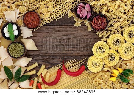 Spaghetti pasta selection and italian food ingredients forming an abstract background border over old oak wood.