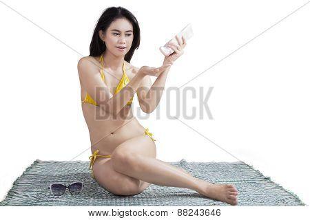 Woman Using Sunscreen In Studio