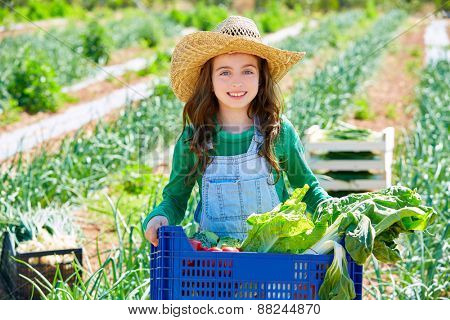 Little kid farmer girl in vegetables harvest at orchard