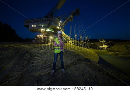 female worker holding signal torch on backgroud of career stacker