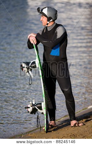 Male wakeboarder posing with his board half-face