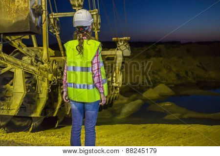 female worker lookis at sandpit on backgroud of career stacker