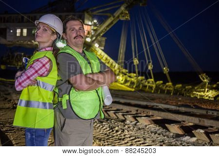 two workers stand back to back  on background of career stacker