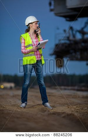 female worker talking on walie-talkie with folder on sand on backgroud of career stacker