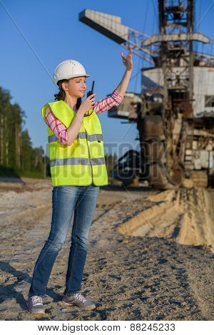 female worker talking on a walkie-talkie on a background of career Stacker
