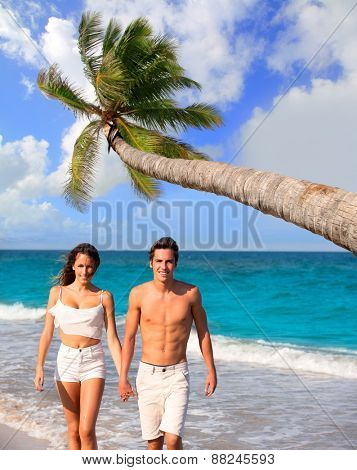 Couple of young tourists walking in a tropical summer beach with coconut palm trees