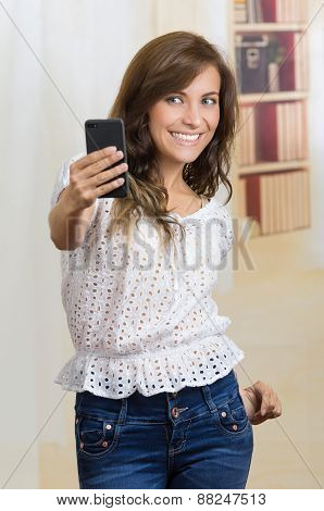 young beautiful hispanic woman using her cell phone taking a selfie